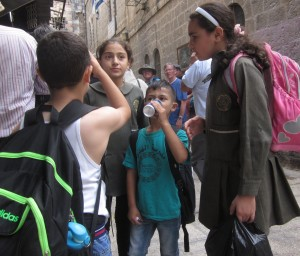 A group of Muslim children stop for refreshment.