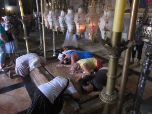 Pilgrims reverence a rock slab connected with the burial of Jesus.