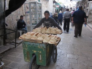 A boy delivers bread in the old city.