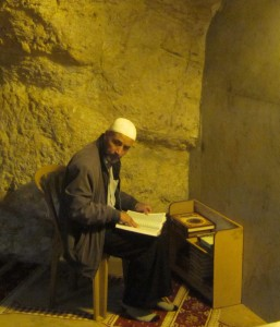 A man prays in the grotto.